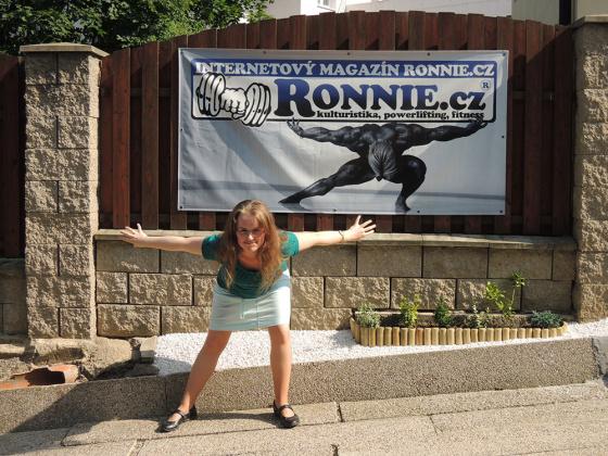 Žena stojí před reklamním bannerem.